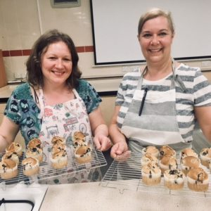 Two women holding tray of muffins