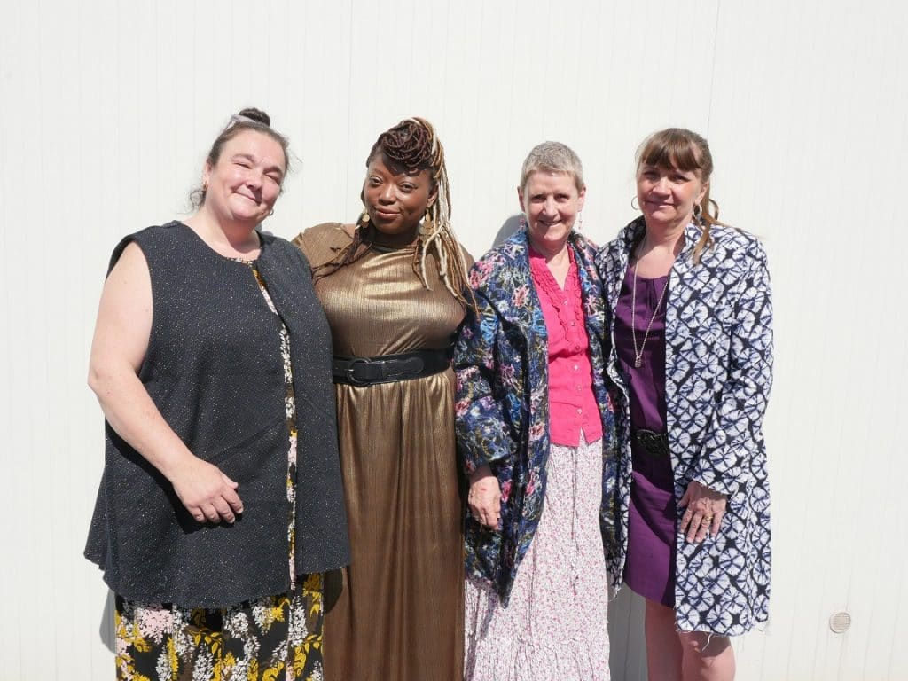 Four women standing against a wall modelling their handmade clothes